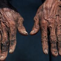 Indonesia, Bali,  Woman's weathered hands while harvesting sea salt