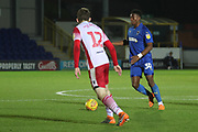AFC Wimbledon defender Paul Kalambayi (30) taking on Stevanage defender Steve Seddon (12) during the EFL Trophy group stage match between AFC Wimbledon and Stevenage at the Cherry Red Records Stadium, Kingston, England on 6 November 2018.