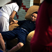 "Jeans factory boss Mr Yang enjoys a massage in Zhongshan city, China. .This picture is part of a photo and text story on blue jeans production in China by Justin Jin. .China, the ""factory of the world"", is now also the major producer for blue jeans. To meet production demand, thousands of workers sweat through the night scrubbing, spraying and tearing trousers to create their rugged look. .At dawn, workers bundle the garment off to another factory for packaging and shipping around the world..The workers are among the 200 million migrant labourers criss-crossing China.looking for a better life, at the same time building their country into a.mighty industrial power."