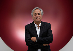 © Licensed to London News Pictures. 09/10/2012. LONDON, UK. Artist Anish Kapoor stands in front of his sculpture 'Hollow' (2012) at a press view ahead of his new exhibition at the Lisson Gallery in London today (09/12/12) . The exhibition, the first since the artists solo exhibition at the Royal Academy of the Arts in 2009, features new works by Kapoor and runs from the 10th of October to the 10th of November 2012. Photo credit: Matt Cetti-Roberts/LNP