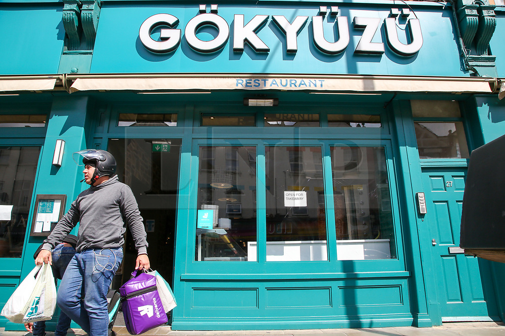 """© Licensed to London News Pictures. 24/05/2020. London, UK. An Uber Eats driver leaves 'GOKYUZU' a Turkish restaurant on Green Lanes, Haringey in north London which is open for take away only, as Muslims celebrate Eid al-Fitr. On Eid al-Fitr also known as """"Festival of Breaking the Fast"""", a religious holiday celebrated by Muslims worldwide that marks the end of the month-long fasting of Ramadan, restaurants would normally be packed with people celebrating Eid. Photo credit: Dinendra Haria/LNP"""