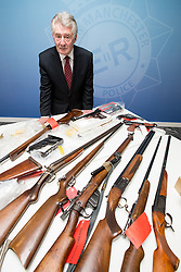 © Licensed to London News Pictures . 07/08/2014 . Manchester , UK . Greater Manchester's Police and Crime Commissioner , Tony Lloyd , with some of the haul . Greater Manchester Police displays some of the cache of firearms and ammunition they collected during a two week firearms amnesty in July , at the force's North Manchester headquarters , this morning (7th August 2014) . GMP reports collecting 225 firearms and over 3000 rounds of ammunition during the fortnight amnesty of which , they say, over 80 of the weapons were illegally owned . Amongst the haul were rifles, shotguns , handguns and air weapons as well as imitation and antique firearms . Photo credit : Joel Goodman/LNP