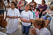 22 JULY 2010 -- PHOENIX, AZ: L to R: Maria Nowakowski (CQ), Georgina Sanchez (CQ), Maria Uribe (CQ) and others pray at an alter for the Virgin of Guadalupe in front of the courthouse Thursday. Thousands of people came to the Sandra Day O'Connor United States Courthouse (CQ) in downtown Phoenix Thursday. PHOTO BY JACK KURTZ