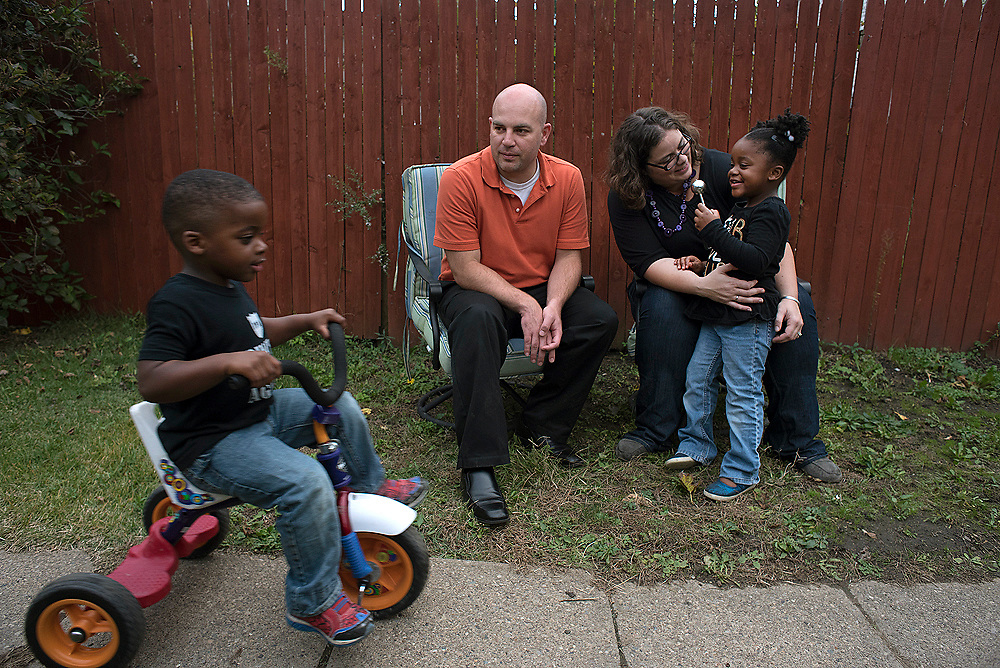 Josh and Meg McKivigan play with two of their three adopted children twins Ezra and Naomi in the backyard of their Bellevue home.