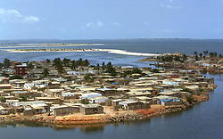 Homes that Angolans live in are in sharp contrast to the homes for foreigners and government officials in the capital of Luanda in Angola in this file photo.  President Jose Eduardo dos Santos, who has led Angola since 1979, said he would not run in presidential elections planned for next year.  Angola's brutal 26 year-civil has displaced around two million people - about a sixth of the population - and 200 die each day according to United Nations estimates. .(Photo by Ami Vitale)