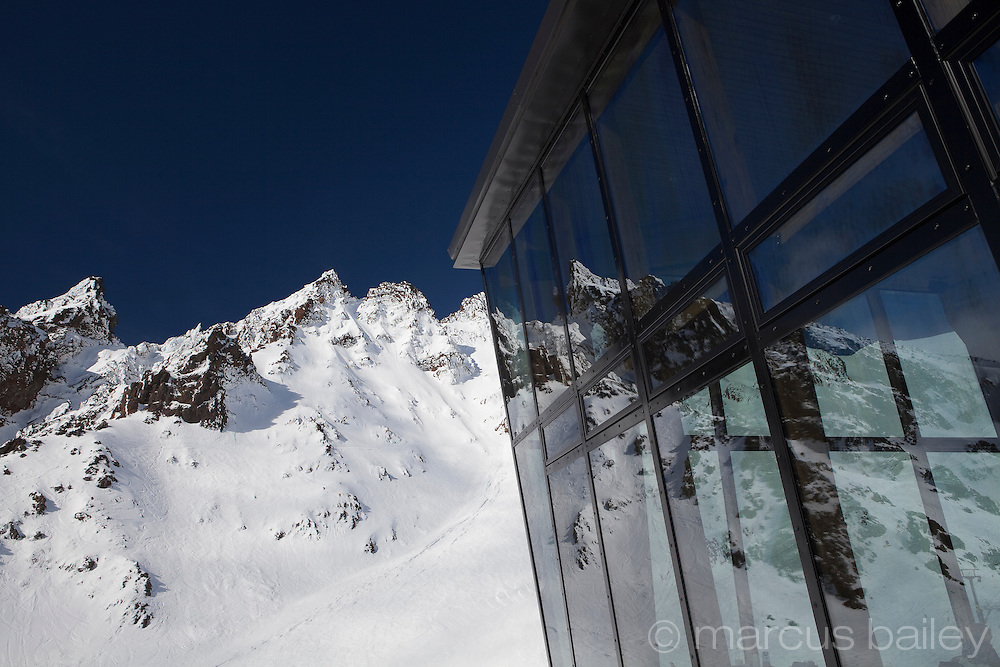 blue sky mountain reflections in this stunning glass cafe on mt ruapehu, tongariro national park, new zealand