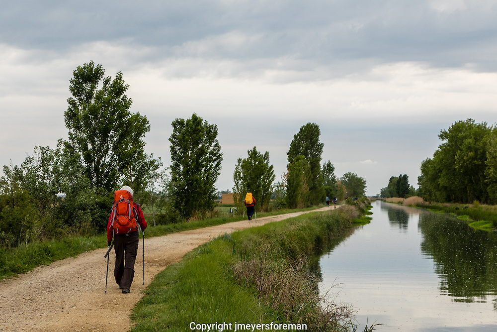 the pilgrims walking the Camino Frances walk near the beautiful Canal de Castlla, once used for grain trasport they now are only used for irrigation.