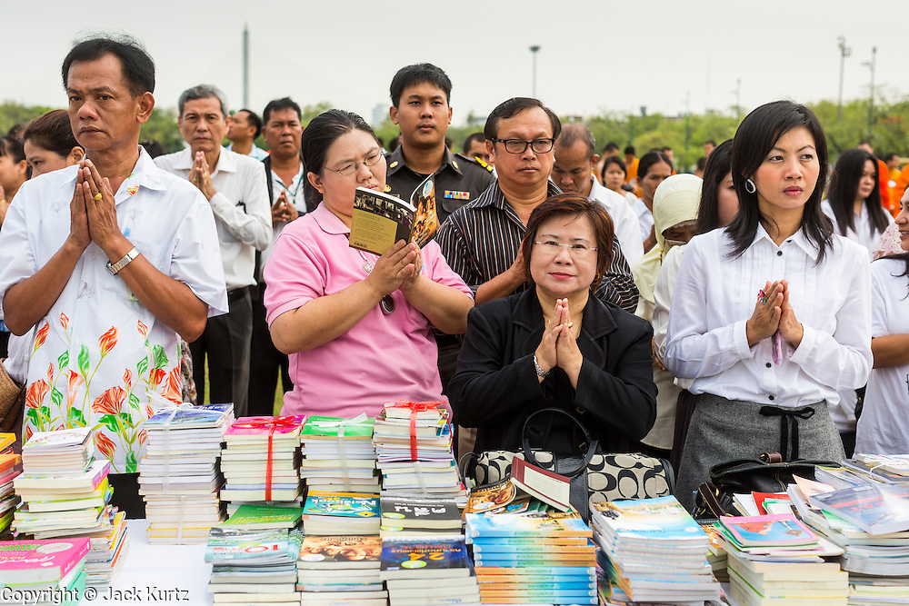 """23 APRIL 2013 - BANGKOK, THAILAND:   A Thai woman reads while everyone around her prays during the opening ceremony to mark Bangkok as the World Book Capital City 2013. UNESCO awarded Bangkok the title. Bangkok is the 13th city to assume the title of """"World Book Capital"""", taking over from Yerevan, Armenia. Bangkok Governor Suhumbhand Paribatra announced plans that the Bangkok Metropolitan Administration (BMA) intends to encourage reading among Thais. The BMA runs 37 public libraries in the city and has modernised 14 of them. It plans to build 10 more public libraries every year. Port Harcourt, Nigeria will be the next World Book Capital in 2014..PHOTO BY JACK KURTZ"""