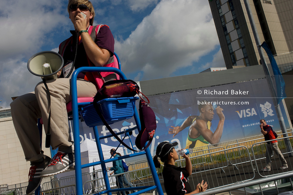 A Games Maker volunteer uses a megaphone to entertain spectators passing a Usain Bolt Visa billboard  during the London 2012 Olympic Park during the games. London 2012 volunteers are called 'Games Makers', as they are helping to make the Games happen. Up to 70,000 Games Makers take on a wide variety of roles across the venues: from welcoming visitors; to transporting athletes; to helping out behind the scenes in the Technology team to make sure the results get displayed as quickly and accurately as possible. Games Makers come from a diverse range of communities and backgrounds, from across the UK and abroad. The vast majority are giving up at least 10 days to volunteer during the Games.