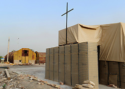 "© licensed to London News Pictures. HELMAND, AFG  21/04/11. The chapel at the base surrounded by the Hesco Bastion fortified walls. A British Army chaplain from Sidmouth who is due to finish his tour this Easter Sunday has proved a hit with paratroopers in Helmand Province, handing out crosses made from the wire-mesh that surrounds their base. Padre Robin Richardson (40) a member of 3rd Battalion The Parachute Regiment, has been serving in Afghanistan for the last six months. ""Towards the beginning of the tour, some of the lads asked me if I had some crosses I could give them,"" he said. ""I found a few at Camp Bastion, and I gave them out. I ran out very quickly.""..""So I wandered around our camp at Shahzad, trying to find something I could fashion into a cross. I noticed some discarded Hesco wire, and I saw lots and lots of crosses"". The wire normally makes up part of the Hesco Bastion fortified walls,  mesh containers with thick liners filled with gravel - that surround military bases across Afghanistan. ""I got busy with some bolt-cutters and a hammer and a drill,"" said Robin. ""And I started making small crosses out of the discarded wire.""..""A lot of the lads have asked if they can have one,"" he said. ""And they've been wearing them, and understanding a bit about what lies behind it"". Robin will be returning home to be reunited with his family after six months. ""I've got three sons, aged 13, 11 and 7, and they're fab,"" he said. ""They give my heart a reason for beating every morning"". ""The thing I've missed the most has been their smiles"" he added. ""The first thing I'll do when I get home is give them a hug"".. Please see special instructions for usage rates. Photo credit should read SGT Alison Baskerville/LNP"