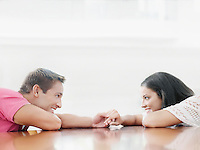 Young couple holding hands across table and looking into each other's eyes