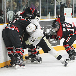 TRENTON, ON - Apr 18, 2016 -  Ontario Junior Hockey League game action between Trenton Golden Hawks and the Georgetown Raiders. Game 3 of the Buckland Cup Championship Series  at the Duncan Memorial Gardens in Trenton, Ontario. Blayne Oliver #16 of the Trenton Golden Hawks and Andrew Court #88 and Daniel Hardie #15 battle for the puck along the boards during the third period.(Photo by Tim Bates / OJHL Images)