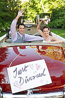 Happy couple in a convertible car waving with just divorced sign on it