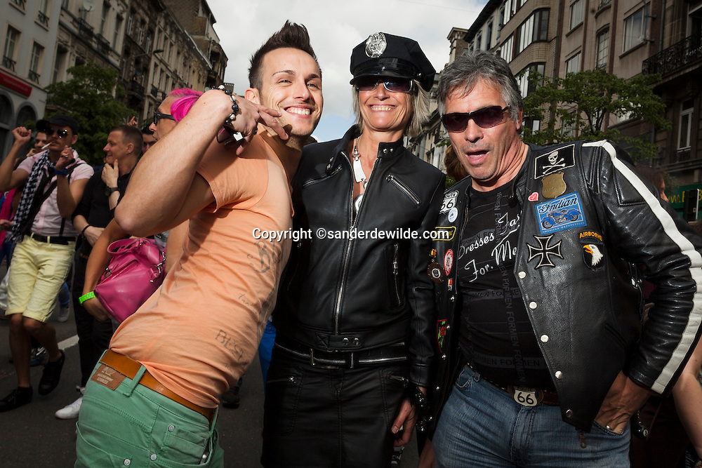 Participants of a gay pride parade in Brussels. Two men and a woman, dressed as an police officer