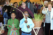 From left, children, Venice Dennis and Mentorl Zorya (glasses) carry palm leaves with other unidentified parishioners at St. Michael the Archangel Catholic Church after Palm Sunday services Sunday April 9, 2017 in Levittown, Pennsylvania. Palm Sunday commemorates Jesus' triumphal entry into Jerusalem. (Photo by William Thomas Cain)