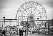 A family stands by the fence of the Wonder Wheel at Coney Island. The Wonder Wheel was built in 1920 by the Eccentric Ferris Wheel Company.
