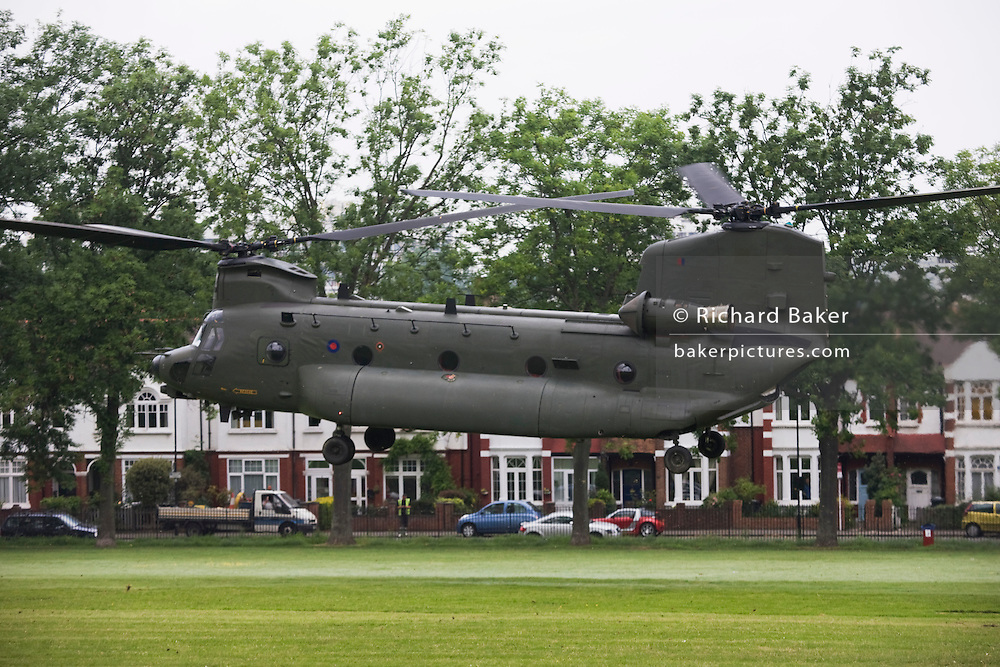 With Edwardian homes nearby, Boeing-built HC2 Chinook RAF helipcopter performs a recce in Ruskin Park, a south London open space