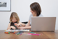 Mother playing with daughter (3-4) open laptop on table