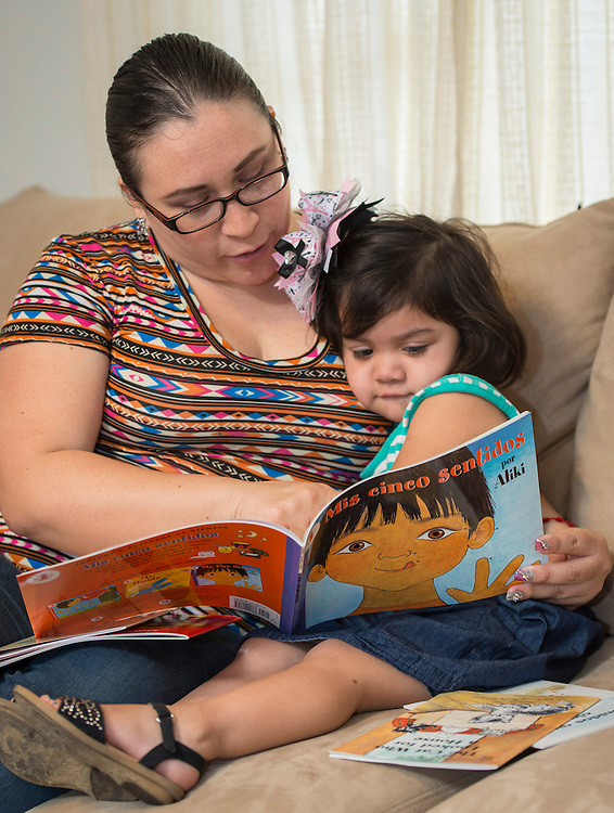Nelly Salazar and her daughter, Bibi, look at a book at their home, March 26, 2014. The Salazars are participating in the Home Instruction for Parents of Pre-K Youth (HIPPY) program.
