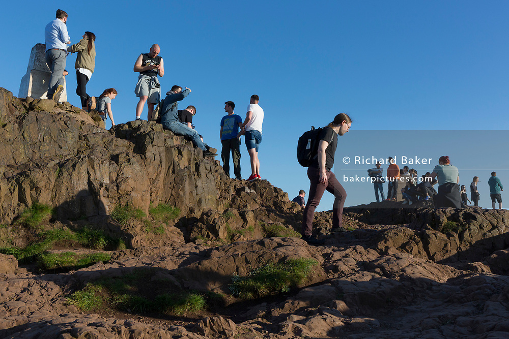 """Walkers enjoy summer evening sunshine on the summit of Arthur's Seat in Holyrood Park, overlooking the city of Edinburgh, on 26th June 2019, in Edinburgh, Scotland. Arthur's Seat is an extinct volcano which is considered the main peak of the group of hills in Edinburgh, Scotland, which form most of Holyrood Park, described by Robert Louis Stevenson as """"a hill for magnitude, a mountain in virtue of its bold design"""". The hill rises above the city to a height of 250.5 m (822 ft), providing excellent panoramic views of the city and beyond."""