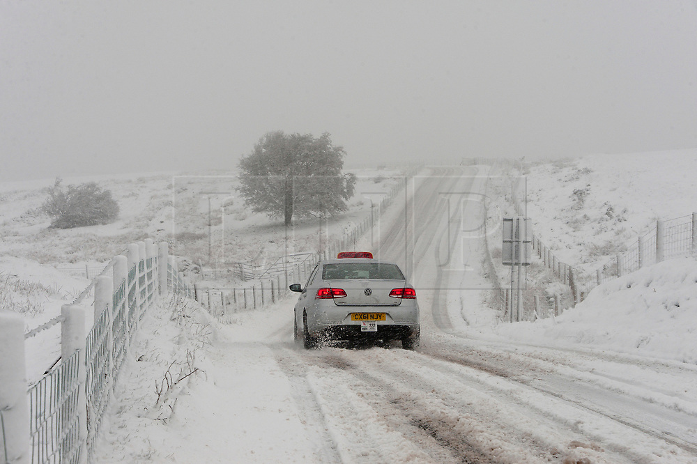 © Licensed to London News Pictures. 04/04/2019. Builth Wells, UK. Motorists drive along the B4520 road through blizzard conditions on the Mynydd Epynt range between Builth Wells and Brecon in Powys, UK. Photo credit: Graham M. Lawrence/LNP
