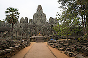 A landscape view of Bayon Temple which stands in the centre of the walled temple complex of Angkor Thom, Siem Reap Province, Cambodia, South East Asia.  The temple was built around 1190 AD by King Jayavarman VII as a Buddhist temple, but it incorporates elements of Hindu cosmology.  In the centre is a statue of Buddha with a yellow tunic.  (photo by Andrew Aitchison / In pictures via Getty Images)