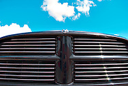 The front grille of a black Dodge Ram pickup truck with sky background. WATERMARKS WILL NOT APPEAR ON PRINTS OR LICENSED IMAGES.