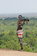 Young male Karo tribe boy with AK-47 rifle . Omo Valley, Ethiopia