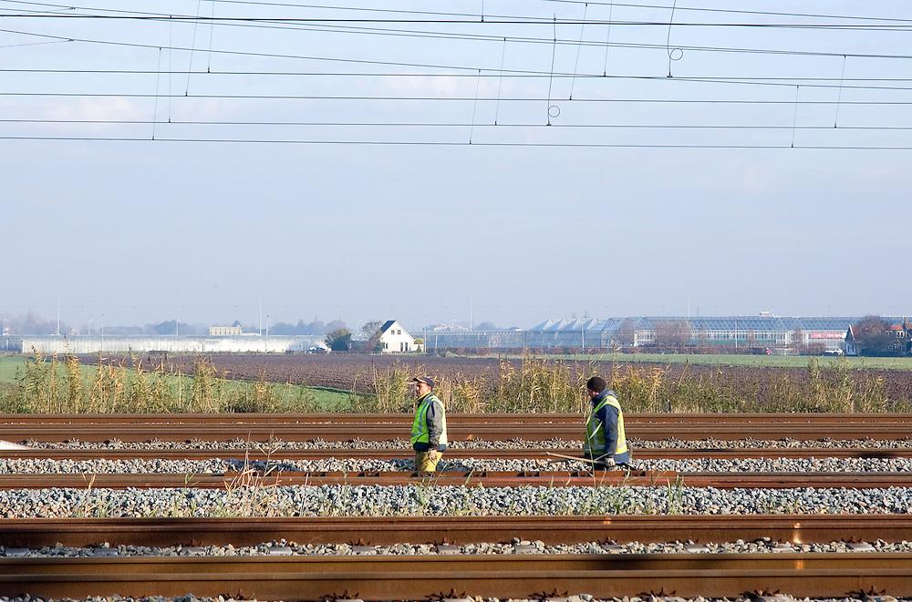 Nederland, Barendrecht, 20051130..Rangeerterrein Kijfhoek..Baanwerkers lopen tussen de sporen.