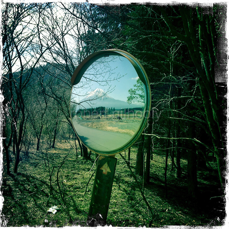 Mt Fuji is reflected in a roadside mirror along a trail that takes trekkers through parts of the Asagiri Plateau, with almost uninterrupted views of Mt Fuji, in Shizuoka Prefecture Japan on 22 March 2013.  Photographer: Robert Gilhooly