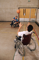 Two men with disabilities; who are wheelchair users; playing game of basketball in sports hall,