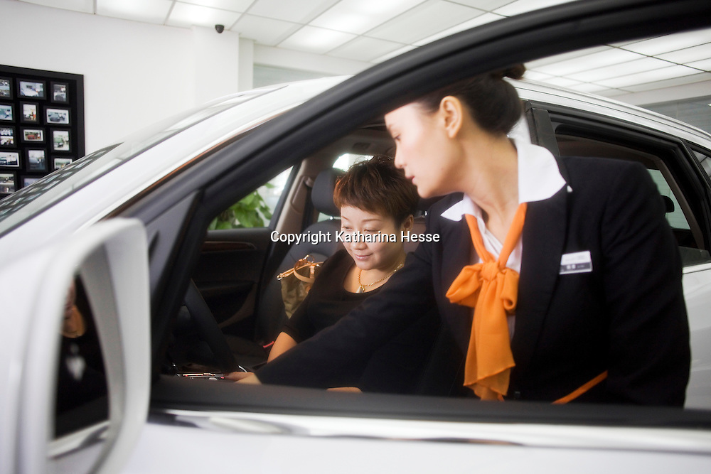 CHENGDU, 10/17/2012 :  Geschaeftsfrau Yang Xi, 37, laesst sich ihren neuen Wagen von einer Audimitarbeiterin vorfuehren .