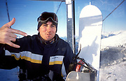 A snowboarder, in ski lift, gesturing to camera, Les Trois Vallees, Meribel, France, 2004