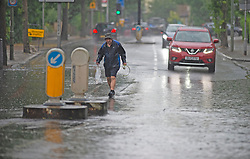 ©Licensed to London News Pictures 17/06/2020<br /> Bromley, UK. An elderly man crossing the road. Widmore Road in Bromley, South East London is flooded in both direction due to heavy rain. Torrential rain and thunderstorms across large parts of the UK today as the sunny weather takes a break. Photo credit: Grant Falvey/LNP