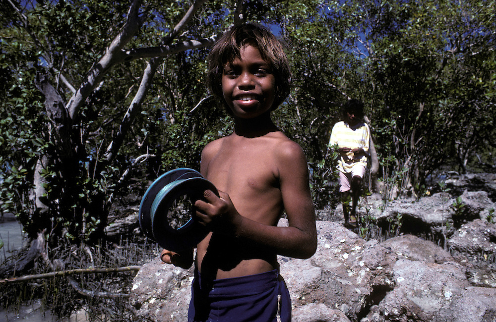Aboriginal boy fishing in the mangroves in Broome, The Kimberley, Western Australia