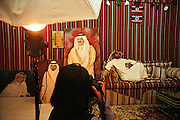 QATAR. Doha. Studio photo...Photocall of a Qatari, in a Bedouin decorum and beside the Emir, Cheikh Hamad Bin Khalifa Al Thani, and his son, the crown prince Cheikh Tamim Bin Hamad Al Thani.