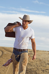 portrait of a very good looking cowboy in New Mexico walking on a dirt road