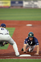 12 August 2011: Kevin Smith holds Tyler McNeely close to the first base bag  during a game between the Rockford River Hawks and the Normal Cornbelters at the Corn Crib in Normal Illinois.