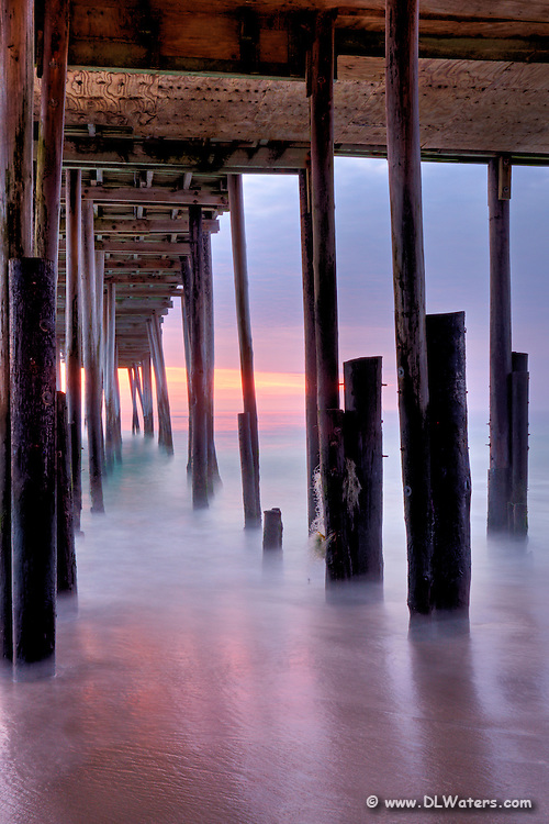 A long exposure turns the motion of waves into mist at Kitty Hawk Fishing Pier.