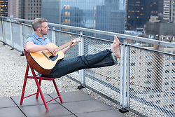 man on a rooftop in New York City playing guitar