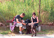 Couple age 22 sitting on bench playing with dog.  Gdynia Poland