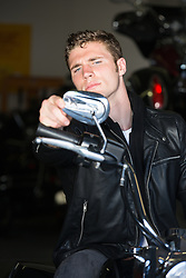 All American man sitting on a Motorcycle in an auto repair shop
