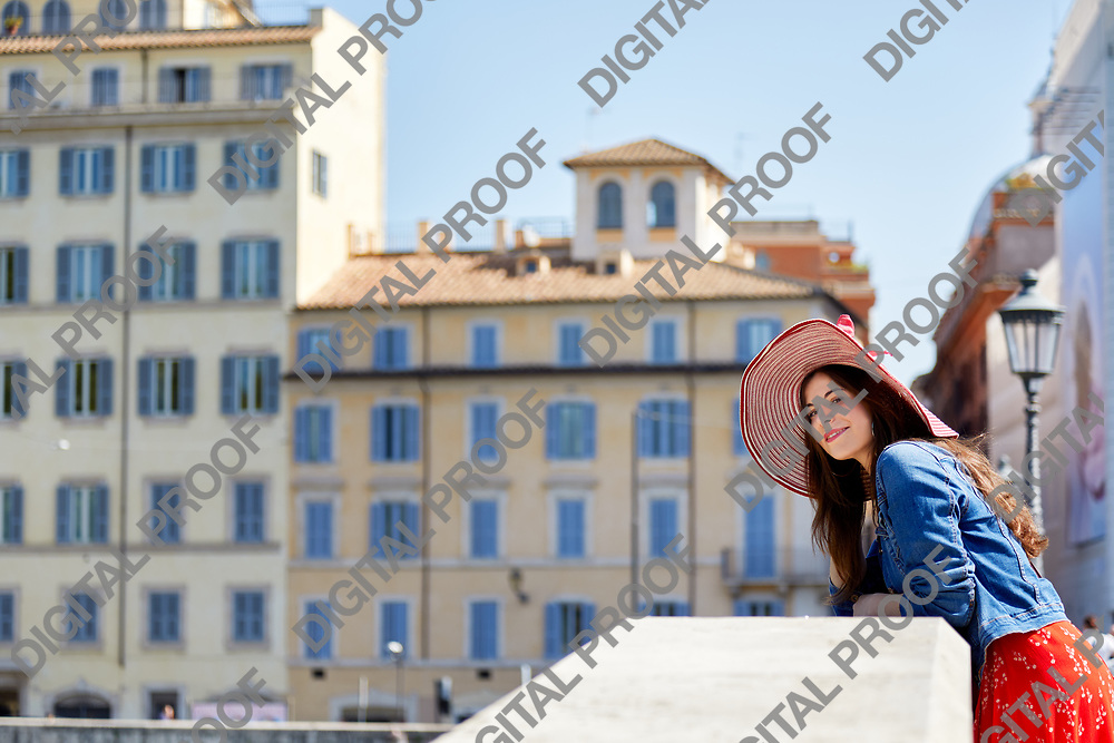 Side view of woman tourist leaning on handrail of the bridge on sunny town street.