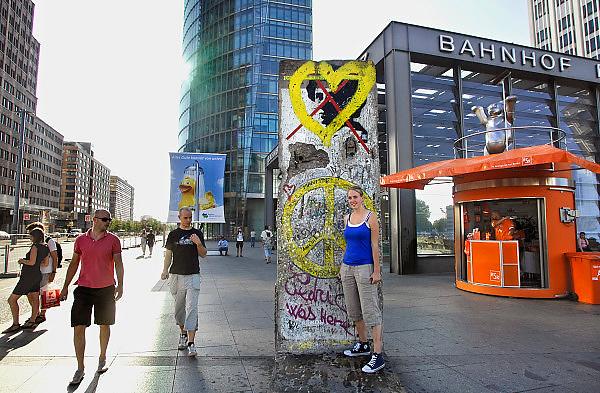 Duitsland, Berlijn, 22-8-2009Een meisje, toerist, laat zich fotograferen bij een origineel stuk van de Berlijnse muur op de Potsdamer Platz, het nieuwe centrum van de stad waar tot 1989 een niemandsland was.Foto: Flip Franssen/Hollandse Hoogte