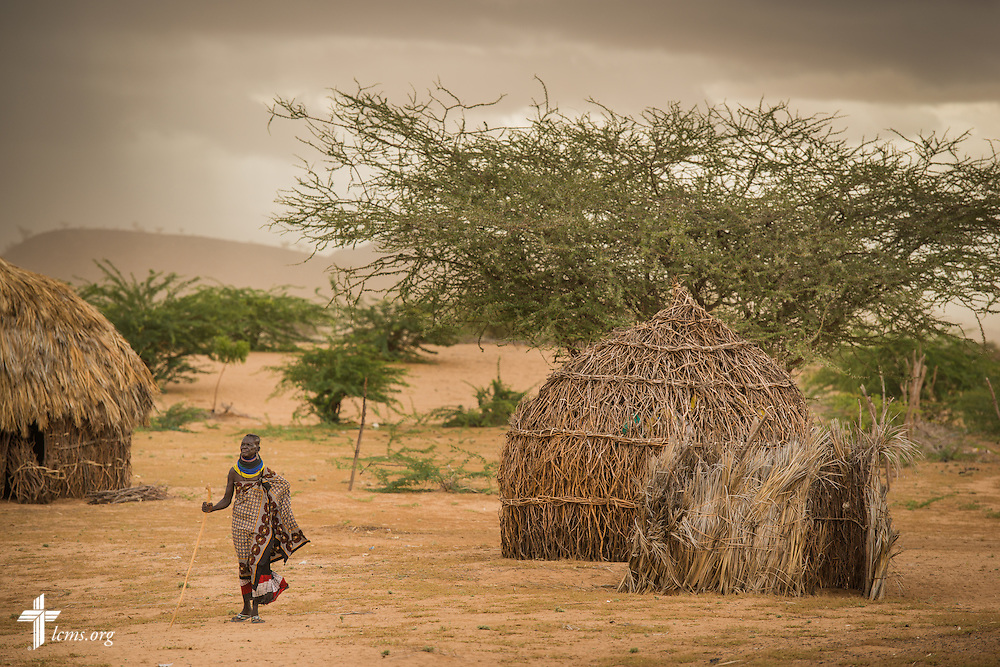 Under a stormy sky, a woman walks to the LCMS Mercy Medical Team on Tuesday, June 21, 2016, in Nataparkakono, a village in Turkana, Kenya.  LCMS Communications/Erik M. Lunsford