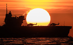 © Licensed to London News Pictures. 16/08/2017. Portsmouth, UK. The sun rises behind the Royal Navy's new aircraft carrier HMS Queen Elizabeth on The Solent as she nears her home port of Portsmouth for the first time. The new ship at 65,000 tonnes is the biggest warship ever built in the UK. Photo credit: Peter Macdiarmid/LNP
