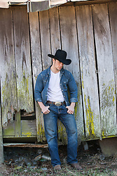 hot cowboy leaning against a rustic barn