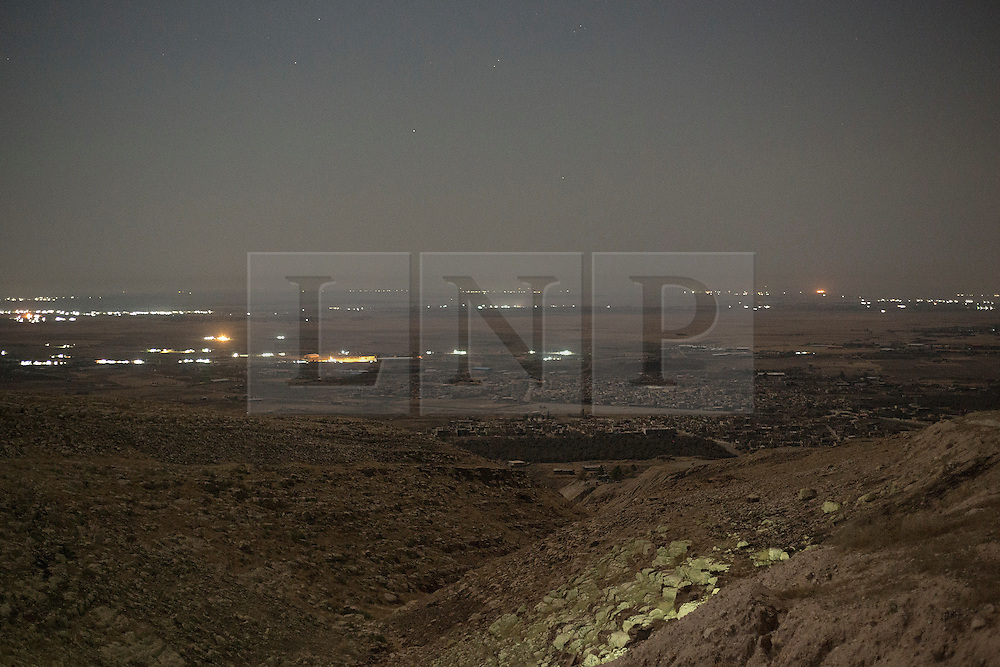 © Licensed to London News Pictures. 02/09/2015. Bashiqa, Iraq. Illuminated sections of the ISIS held Iraqi town of Bashiqa, and the distant lights of Mosul, are seen from peshmerga positions on Bashiqa Mountain, Iraq. The Islamic State leaves certain parts of Bashiqa town illuminated in an attempt to coax coalition airstrikes in to areas of the town away from their positions.<br /> <br /> Bashiqa Mountain, towering over the town of the same name, is now a heavily fortified front line. Kurdish peshmerga, having withdrawn to the mountain after the August 2014 ISIS offensive, now watch over Islamic State held territory from their sandbagged high-ground positions. Regular exchanges of fire take place between the Kurds and the Islamic militants with the occupied Iraqi city of Mosul forming the backdrop.<br /> <br /> The town of Bashiqa, a formerly mixed town that had a population of Yazidi, Kurd, Arab and Shabak, now lies empty apart from insurgents. Along with several other urban sprawls the town forms one of the gateways to Iraq's second largest city that will need to be dealt with should the Kurds be called to advance on Mosul. Photo credit: Matt Cetti-Roberts/LNP