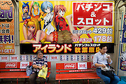 A man and a woman having a snack in front of a poster with anime characters, advertising a patsinko parlor, in Akihabara district of Tokyo on Thursday 12th of October 2006.