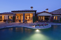 View of luxury villa with swimming pool in evening